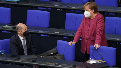 German Chancellor Angela Merkel talking with Finance Minister Olaf Scholz inside the Bundestag.