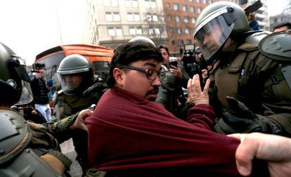 A protestor is arrested in Santiago on Monday.