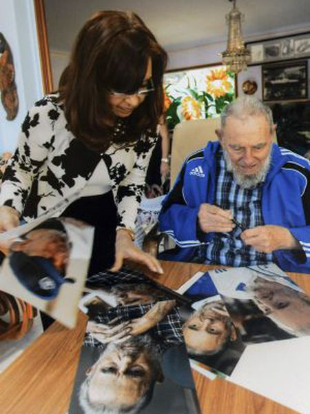 Cuba's former President Fidel Castro signs pictures for Argentinian President Cristina Fernández de Kirchner in Havana in this handout image.