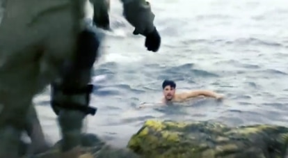 A man reaches the Spanish shore after swimming in from Moroccan territory.