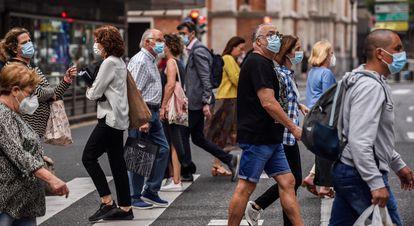 Pedestrians cross a street in Bilbao.