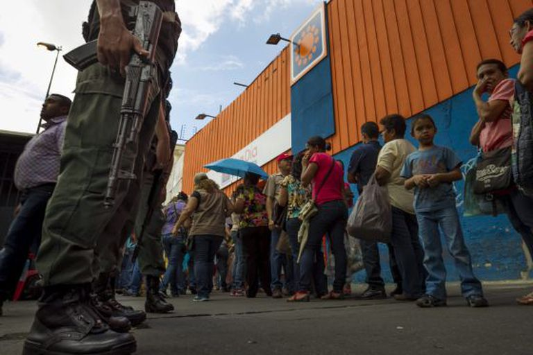 People stand in line outside a supermarket in Venezuela.