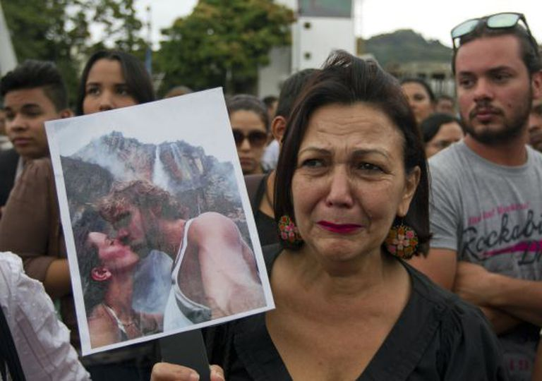 A woman holds up a photograph of Mónica Spear and her ex-husband at a rally in Caracas.