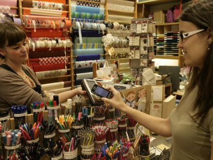 A customer using her cellphone to pay in a store in Sitges.