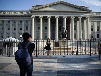 A tourist poses in front of the Treasury Department building in Washington DC.