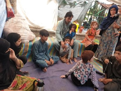 Gul Khan (left, holding her hand to her face) and members of her family at Shahr-e Now Park in Kabul, where they have been living for two months.