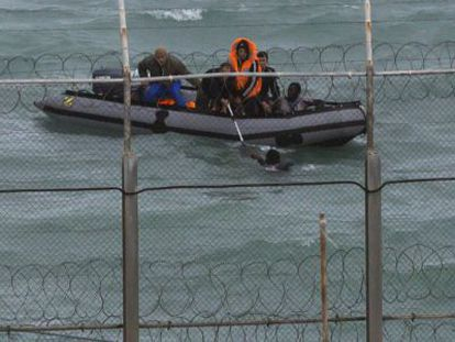 Moroccan soldiers help an immigrant in waters close to Ceuta.