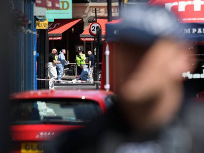 Police officers look for evidence at an attack site in London.
