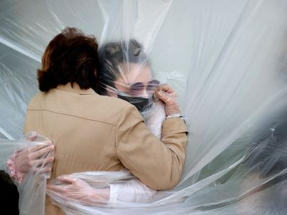 A woman hugs her grandmother through a plastic sheet in New York, in May 2020.