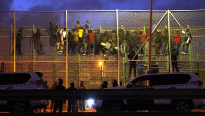 A group of migrants attempting to jump the border fence in Melilla in October  2014.