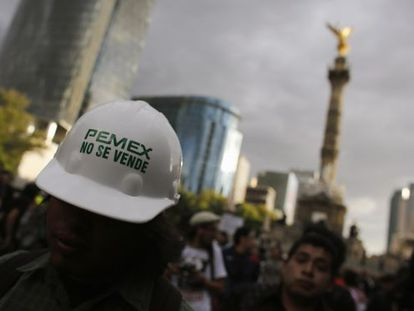 """A protestor wears a hardhat that reads: """"Pemex is not for sale."""""""
