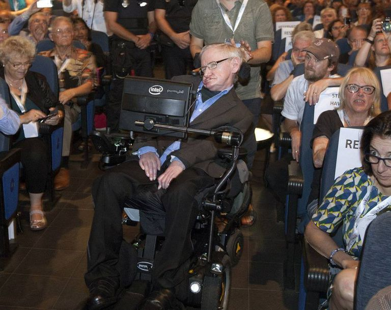 Stephen Hawking arrives onstage with Spanish police standing by.
