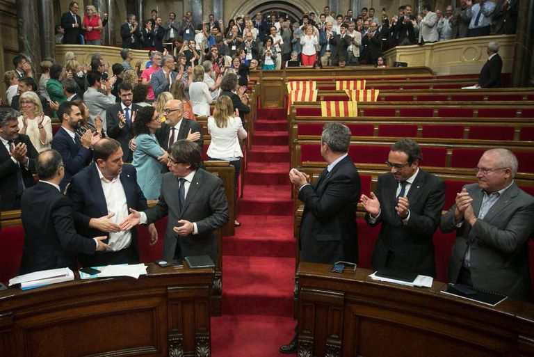 Catalan deputies applaud the passing of the referendum law in a half-empty regional parliament.