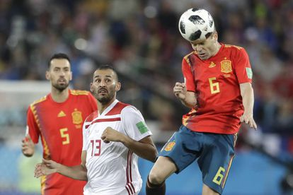 Iniesta heads the ball as Boutaib and Busquets look on.