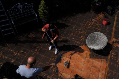 Residents clean up the ash from the volcano in the yard of their house on La Palma, Spain on Thursday.
