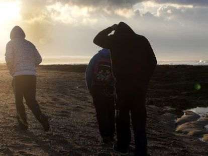 A group of men search for hash on a beach in Chiclana.
