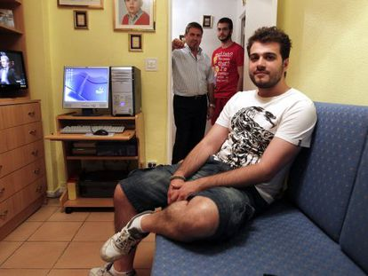 David Sánchez, 27 years old sits in his room with his brother Víctor (22), behind, and their father Francisco.