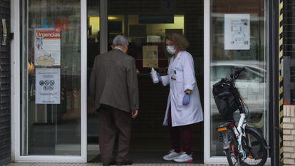 A worker offers antibacterial gel to a man walking into the Estrecho de Corea health center in Madrid.