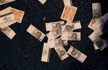 Fake 100-peso bills with a picture of President Cristina Fernández de Kirchner lie on the ground after a protest outside Congress.