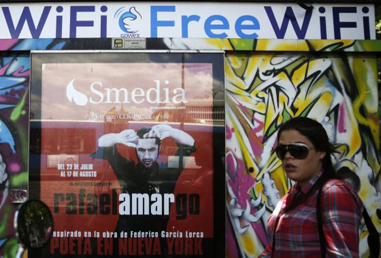 A woman walks past a newspaper kiosk joined to the Gowex wi-fi network in Madrid.