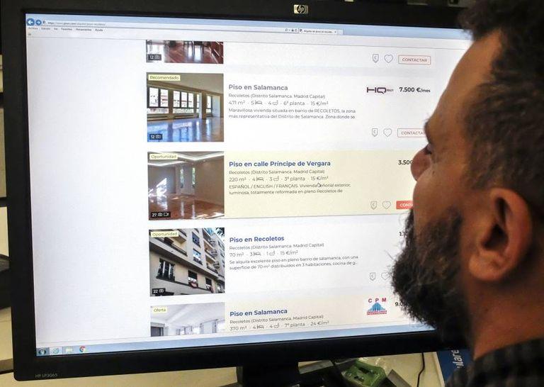 A man looks up flats on Internet.