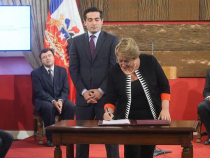 Bachelet signs a presidential decree under the watchful gaze of Peñailillo.