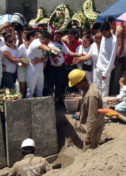 Juan Carlos Ortiz empties a bottle of whisky on his brother's grave.