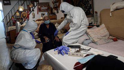 Healthcare workers examine suspected coronavirus patient at her home in Madrid.