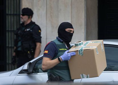 A Civil Guard officer takes away material seized from a home in Sabadell.