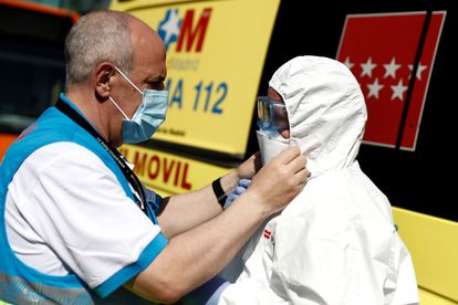 Healthcare personnel help disinfect two buses used to shuttle Covid-19 patients between hospitals.