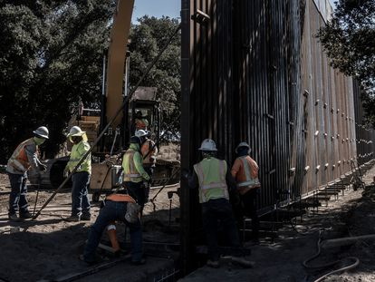 Workers erecting the new border wall in the desert of Baja California.
