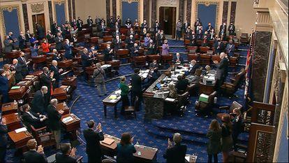 Senators applaud ahead of the final vote of Covid-19 relief bill on Saturday.