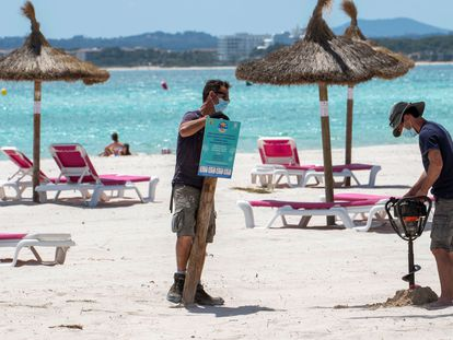 Workers putting up an information sign at the beach in Alcúdia, Mallorca on May 12.
