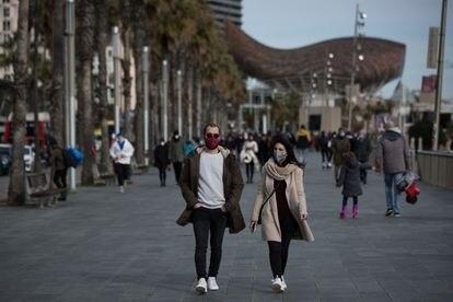 People wearing masks on the seaside promenade in Barcelona.