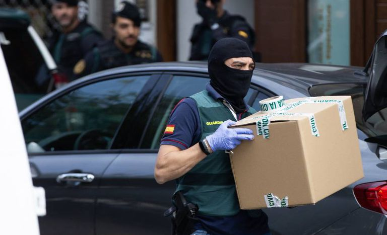 A Civil Guard officer takes material from one of the homes raided on Monday.