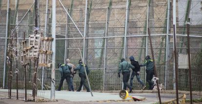 Spanish Civil Guard officers march two immigrants back to Morocco on February 19.