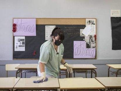 A cleaner wearing a mask prepares a classroom in Barcelona.