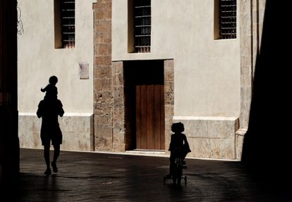 A man walks outside with his two children in Valencia.
