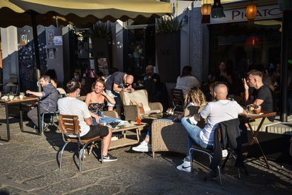 People sit in a restaurant's outdoor seating area in Milan, Italy, on Wednesday.