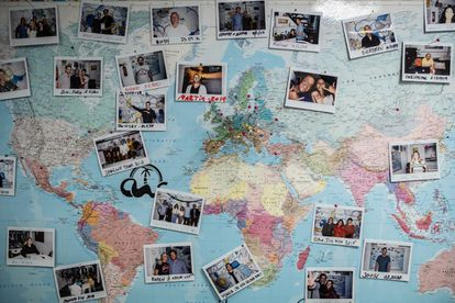 A map in a coliving space in Las Palmas de Gran Canaria with photos of the residents pinned to the countries where they are from.