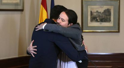 Pedro Sánchez and Pablo Iglesias embrace after signing their agreement on Tuesday.