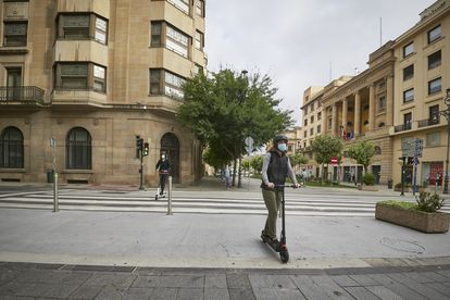 Scooter riders wear face masks in Pamplona, Navarre, where new restrictions have been introduced in one neighborhood.