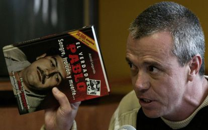 """""""Popeye"""" holding up a book about cartel chief Pablo Escobar."""