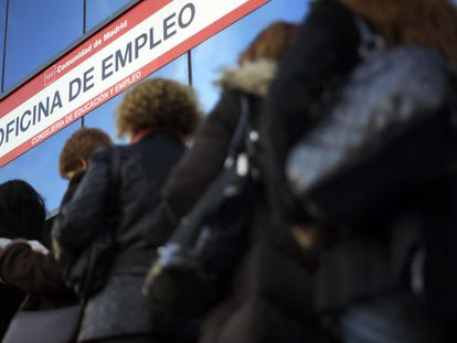 Women stand in line outside an unemployment office.