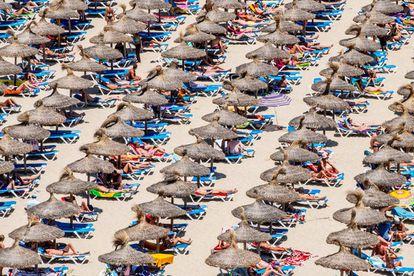 Tourists take in the sun at Magaluf beach in Mallorca.