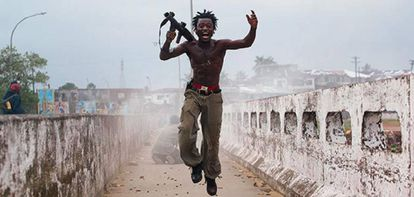 Joseph Duo, when he was a child soldier, leaps after having unloaded a grenade launcher during the civil was in Liberia.