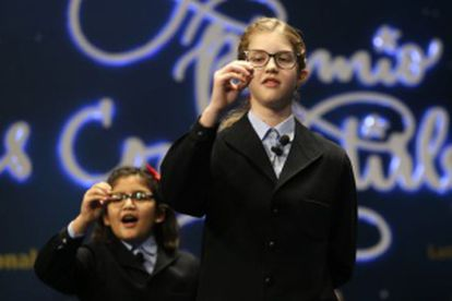 Schoolchildren sing out the prize-winning lottery number.