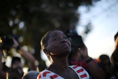 A woman looks on Fidel Castro's funeral motorcade passes by.