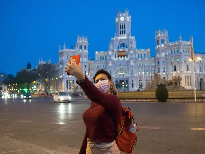 A woman takes a selfie at on the streets of a deserted Madrid.