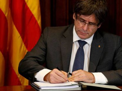 Catalan premier Carles Puigdemont signs the decree officializing the October 1 referendum.